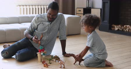 etnia africano : Happy young african ethnicity father in eyeglasses playing dinosaurs wooden bricks with adorable child son at home. Biracial family of two enjoying playtime game activity together in living room.