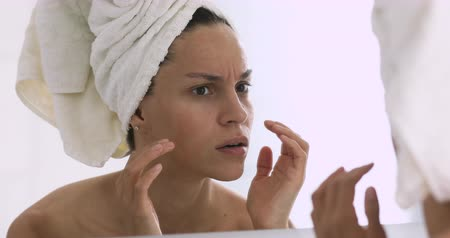 отчаянный : Frustrated young mixed race girl with towel on head looking at mirror, worrying about first wrinkles. Unhappy woman dissatisfied with skincare product effects or skin condition, feeling stressed.