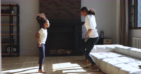 etnia africano : Carefree little african ethnicity kid girl dancing clapping hands with joyful young mother babysitter in living room. Happy small child imitating moves of active mom nanny, having fun at home. Stock Footage