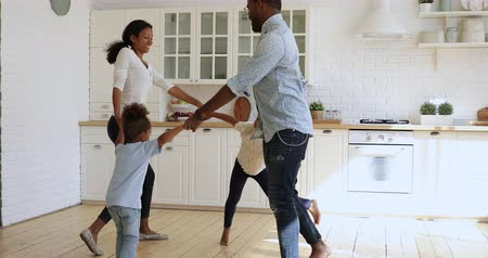 etnia africano : Carefree young african american couple holding hands of joyful kids, dancing in circle barefoot in modern kitchen. Happy mixed race little children siblings having fun fooling around with parents. Stock Footage