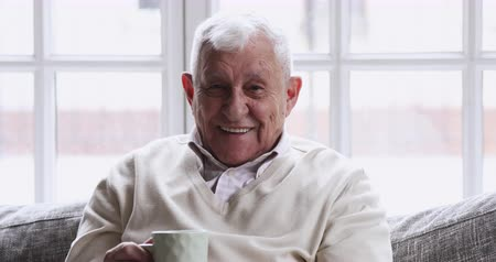 sedmdesátá léta : Happy optimistic elderly senior 80s gray-haired man drinking tea looking away at camera, smiling older adult grandpa healthy teeth rest sit on sofa dream enjoy retirement wellbeing, close up portrait