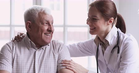 醫療保健 : Caring young female doctor nurse caretaker help talk to happy senior man at medical checkup visit, smiling male old patient get support in hospital at home, elder people healthcare treatment concept