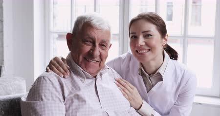醫療保健 : Caring smiling female caregiver embracing happy senior patient looking at camera, young carer or nurse helping old elder care grandpa at nursing home, geriatric medical support concept, closeup portrait