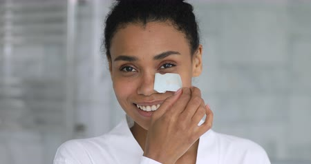 procedimento : Head shot close up happy african american woman using nose cleansing strip. Smiling millennial mixed race lady satisfied with removing blackheads on face, healthy domestic clean skincare concept.