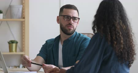 общаться : Happy young male manager in eyeglasses talking to african ethnicity female coworker, sitting together at office desk. Motivated happy multiracial colleagues communicating, discussing working issues. Стоковые видеозаписи