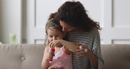 общаться : Head shot happy young nanny holding on lap adorable small child girl wearing crown, blowing soap bubbles at home. Smiling mother enjoying funny activity with cute little daughter on cozy couch.