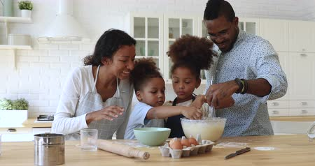 etnia africano : Happy full family having fun preparing pastry together at home. Smiling african dad whisking mixture in bowl while joyful little children adding flour, cooking homemade baking together at kitchen.