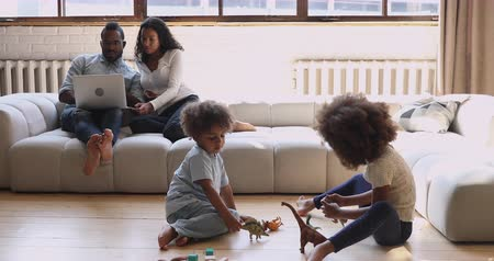 etnia africano : Happy married african american couple relaxing on cozy couch, using laptop shopping online while little cute children siblings playing toys dinosaurs bricks on heated warm wooden floor at home.