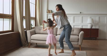 babysitter : Full length overjoyed little child daughter wearing crown princess dress holding hands of smilig young nanny baby sitter mother, dancing twisting together on floor carpet in modern living room.