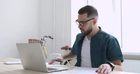 dokumentum : Motivated young male freelancer in eyeglasses doing paperwork, working on computer in office. Confident focused startup entrepreneur businessman using computer software, typing email at workplace.