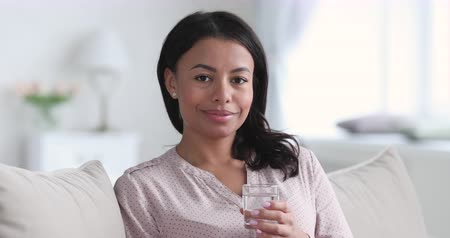 kciuk : Smiling healthy young attractive african american woman sit on sofa hold glass of fresh mineral clean filtered water show thumbs up look at camera recommend hydration for health care concept, portrait Wideo
