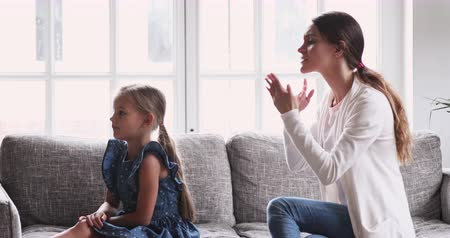 níveis : Angry single mom shouting at preschool kid. Mad young adult mother scolding stubborn fussy little girl close ears ignore punishment at home. Parent disciplining child daughter for bad behavior concept Stock Footage