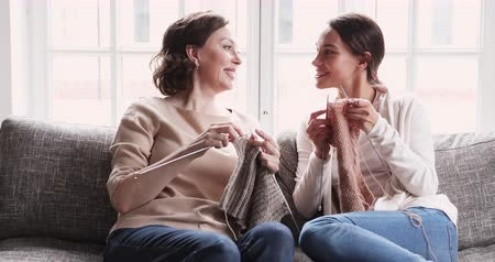 den matek : Friendly happy mature mum and young adult daughter knitting needles together. Happy old mother chatting with daughter. 2 two generation family enjoy leisure handcraft hobby trust talk on sofa at home