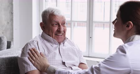 rada : Happy elder male patient listen female doctor at medical visit, smiling healthy senior grandpa talk to young nurse in hospital at nursing home get psychological support, old people healthcare concept