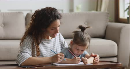puericultura : Pleasant smiling young woman teacher tutor mother nanny embracing small preschool girl daughter, sitting together at table, drawing pictures in album, early children education development concept. Stock Footage