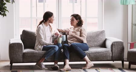 честный : Happy family middle aged old mother and young adult daughter chatting. Mum and grown child rest in cozy living room interior. Smiling two 2 age generations women friends talk drink tea on couch at home