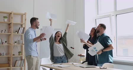 etnia africano : Overjoyed young multiracial team holding papers in hands, celebrating corporate success together in workplace. Excited mixed race employees dancing, tossing documents in air, enjoying office party.