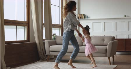 上機嫌 : Carefree happy young mother holding hands lifting joyful small kid daughter, dancing twisting together barefoot on floor carpet at home. Laughing young babysitter having fun with little child girl.