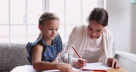 puericultura : Young mom nanny teaching cute kid daughter. Female babysitter and primary school girl drawing pencils together. Happy mommy nanny helping child doing leisure creative education activity concept at home