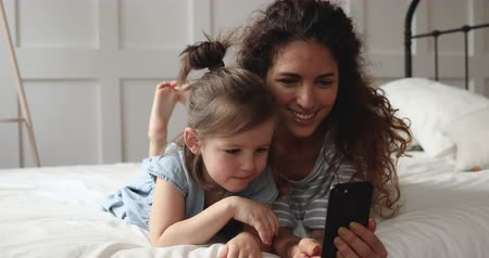 мультфильмы : Joyful young mommy lying on bed with cute little daughter, showing cartoons on smartphone, making funny selfie photos. Happy small preschool kid girl watching using educational mobile apps with mom.