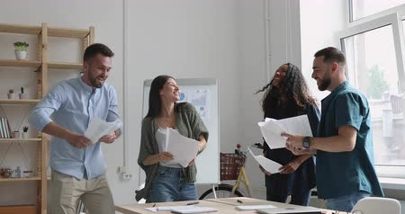 etnia africano : Satisfied with good project results excited young multiracial people having fun together in office. Overjoyed mixed race employees celebrating corporate success at friday party, tossing papers in air. Stock Footage