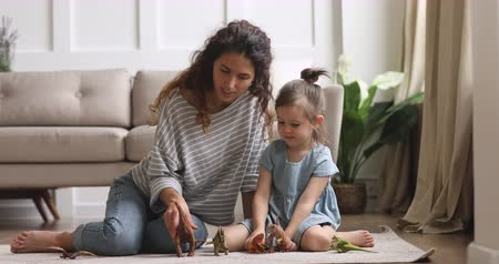 favori : Happy bonding family of two sitting on light floor carpet, playing with dinosaurs toys. Smiling attractive woman babysitter nanny mommy enjoying weekend fun time with small cute daughter kid girl.