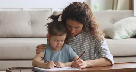 milující : Affectionate young woman babysitter cuddling small cute kid daughter, drawing pictures together in paper album. Happy family of two enjoying creative time together, sitting at coffee table on floor.