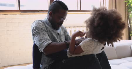 etnia africano : Overjoyed young african american man in eyeglasses playing with cute laughing little preschool daughter on cozy couch. Carefree small child girl having fun with positive biracial father at home.