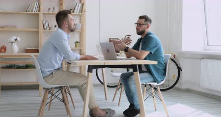 общаться : Full length side view focused young startup hr manager holding job interview with skilled motivated male candidate in modern office. Concentrated businessman in eyeglasses meeting partner client. Стоковые видеозаписи