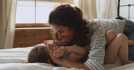 babysitter : Attractive laughing young mother playing peek a boo game with adorable preschool daughter, lying together on bed. Happy mom nanny babysitter having fun in bedroom with cute small playful child girl. Stock Footage