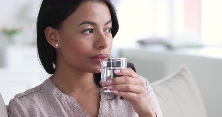 etnia africano : Beautiful healthy young african american woman hold glass drink fresh mineral filtered water sit on sofa at home, thirsty dehydrated lady feel thirst hydrate diet nutrition weigh tloss balance concept