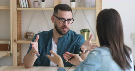 investidor : Focused young male job seeker in eyeglasses talking to female hr manager. Concentrated young businessman consulting with financial advisor lawyer broker insurer at meeting in modern workplace. Vídeos