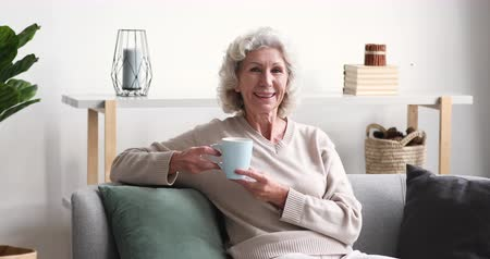 благосостояние : Smiling senior adult lady drinking tea looking away at camera at home. Cheerful retired old grey-haired woman laughing relaxing sitting alone on sofa in cozy living room. Happy elder grandma portrait