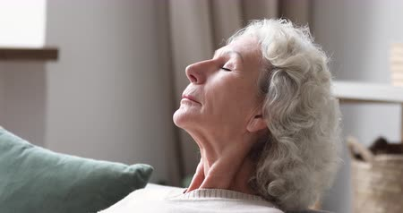 respiração : Closeup side view of serene calm elder woman resting meditating on sofa. Relaxed senior 70 years old lady takes deep breath of fresh air at home. Healthy grandma doing breathing exercise in living room