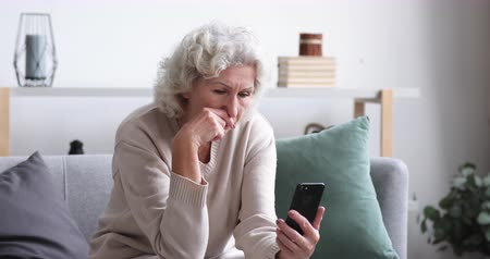 отчаянный : Frustrated senior lady reads bad news in mobile message concept. Sad depressed 70 years old woman looking at smart phone feels shocked. Worried elder female user customer lost money on scam fraud offer