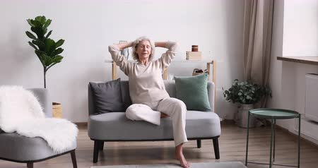 удовлетворения : Happy serene senior adult woman relaxing on comfortable couch. Smiling healthy old lady enjoying retirement slow life in modern cozy living room interior. Relaxed elder european grandma resting at home