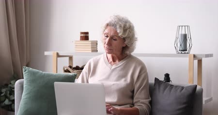 escritor : Inspired thoughtful older lady typing on laptop at home. Elderly 70 years old adult woman using computer thinking of new ideas sit on sofa. Senior female user writing internet blog social media post
