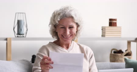 levelezés : Cheerful old senior woman reads postal mail approval letter excited by good news. Excited elder lady feels satisfied with bill or tax refund, bank service offer, holding paper sitting on sofa at home