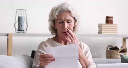 imposto : Shocked upset senior woman reading bad news in post mail letter. Frustrated retired grandma holding bill looking worried about dept, troubled with bankruptcy. Unhappy old lady feels bad surprise concept