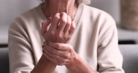 csontok : Senior grandmother massaging hand suffering from joint pain. Older woman having rheumatoid arthritis. Elder adult lady touching wrist feeling hurt. Osteoarthritis geriatric disease concept. Close up view