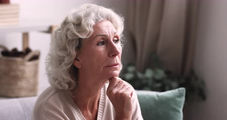 сомнение : Pensive thoughtful senior grandma looking away thinking of solitude. Lonely sad older retired lady feeling melancholic sitting alone on sofa at home. Elder granny reflecting lost in thoughts concept