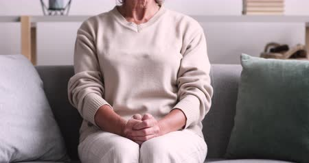 weduwe : Abandoned lonely elder lady sitting on sofa with hands folded. Depressed senior woman feels anxious suffers from solitude. Old arthritic grandma prays alone has geriatric disease concept. Close up view Stockvideo