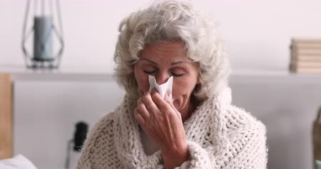 respiratory infection : Sick grey-haired senior woman covered with blanket holding tissue blowing runny nose at home. Ill old grandmother having rheum or seasonal allergy. Elder person caught cold, got flu or sniffles concept