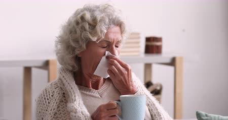 чувствовать : Ill elder woman covered with warm blanket blowing running nose in tissue. Sick senior grandma got flu virus caught cold drinking hot tea at home. Infection disease and old people immune support concept Стоковые видеозаписи