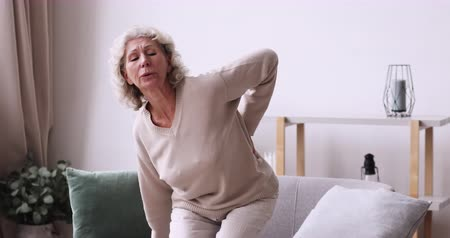 csontok : Tired senior woman feels sudden back pain at home. Unhealthy old lady touching spine muscles having lower lumbar ache sitting on sofa. Upset elder grandma suffering from backache. Osteoarthritis concept
