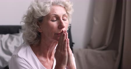 йога : Senior woman spiritual believer praying with eyes closed feeling faith in bedroom. Grateful christian elder grandmother holding hands clasped starting day saying worship prayer concept. Close up view