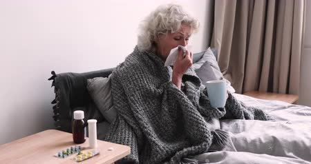 zsebkendő : Ill senior grandma blowing running nose caught cold sits in bed covered with warm blanket. Sick senior woman holding tissue drinking tea having flu virus symptom. Old people influenza treatment concept Stock mozgókép