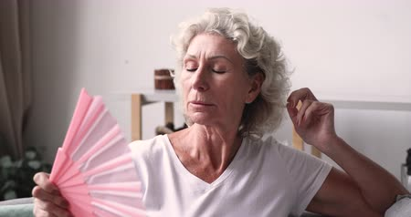 aparelho : Exhausted senior 60s woman suffering from heat summer weather waving fan at home. Elder old grandmother feeling hot and tired, sweating, having menopause health problems, need air conditioner concept Stock Footage