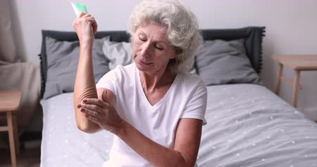 zalf : Smiling older woman applying moisturizer cream on elbow sitting on bed in the morning. Senior lady puts lotion doing everyday body dry skin hydration routine in bedroom. Elderly women skincare concept