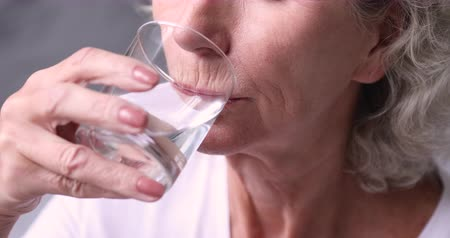 hydratace : Thirsty healthy senior adult woman holding glass drinking fresh mineral pure water. Dehydrated old lady feels thirst hydrates healthcare balance. Elder person morning hydration concept. Close up view